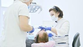 O dentista fêmea com um assistente examina a boca do paciente de um homem de um homem envelhecido Trabalho profissional chave alt vídeos de arquivo