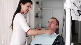 O dentista fêmea de cabelos compridos prepara o paciente masculino para o tratamento dos dentes no fundo do armário do stomatolog video estoque