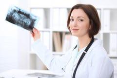 O dentista fêmea moreno novo que senta-se na tabela e examina o raio X dental fotografia de stock