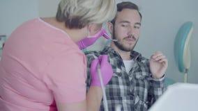 O dentista fêmea na máscara médica e as luvas preparam-se a verificar os tooths do paciente que usa ferramentas médicas O pacient video estoque