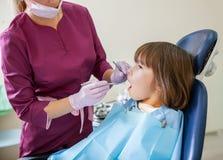 O dentista fêmea no escritório dental trata os dentes com o paciente da criança imagens de stock royalty free