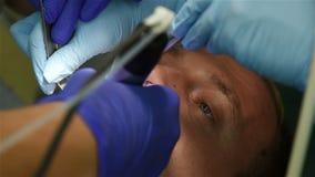 O dentista fura o paciente do adulto do dente filme