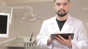 O dentista guarda a tabuleta digital filme