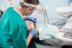 O dentista masculino com ferramentas dentais - espelhe e sonde a verificação acima dos dentes pacientes no escritório dental da c foto de stock