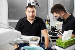 O dentista masculino em um uniforme preto está olhando à câmera quando outro trabalhar com materiais dentais fotos de stock
