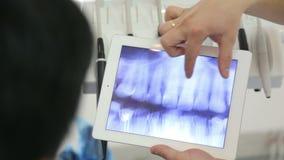 O dentista mostra uma radiografia de um paciente que usa uma tabuleta com um écran sensível filme