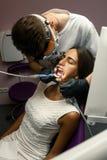 O dentista trata os dentes da jovem mulher que usa ferramentas dentais fotografia de stock