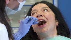 O dentista verifica acima dos dentes do ` s da mulher imagem de stock royalty free