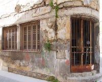 O derelict idoso abandonou a propriedade comercial em um canto com as paredes gastos rachadas de desintegração e as barras de fer imagens de stock