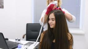 O dermatologista do doutor diagnostica a estrutura do cabelo de uma menina bonita nova com uma ferramenta especial - um trichosco video estoque