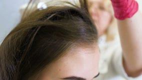 O dermatologista do doutor diagnostica a estrutura do cabelo de uma menina bonita nova com uma ferramenta especial - um trichosco vídeos de arquivo