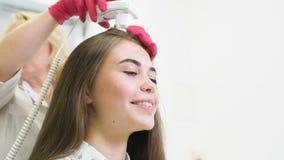 O dermatologista do doutor diagnostica a estrutura do cabelo de uma menina bonita nova com uma ferramenta especial - um trichosco filme