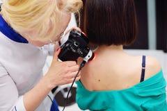 O dermatologista examina as toupeiras ou a acne do paciente com um dermatoscope fotos de stock