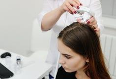 O dermatologista examina um cabelo paciente da mulher usando um dispositivo especial imagens de stock