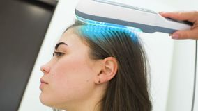 O dermatologista executa o procedimento do pente ultravioleta para curar a psoríase filme
