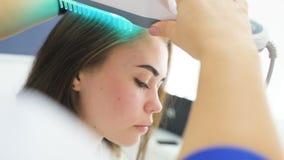 O dermatologista executa o procedimento do pente ultravioleta para curar a psoríase vídeos de arquivo