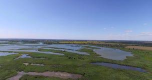O derramamento de um rio pequeno nos campos que cercam vídeos de arquivo