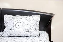 O descanso branco com preto bordou testes padrões em uma cama poderosa do interior do quarto do ébano Fotos de Stock Royalty Free