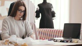 O desenhador de moda brilhante da menina que senta-se em uma tabela no estúdio e tira vídeos de arquivo