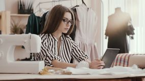 O desenhador de moda da costureira que datilografa na tabuleta, suas mãos está na tabela A menina é cercada por um manequim na vídeos de arquivo