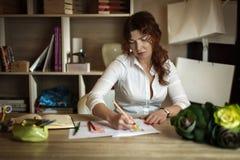 O desenhador de moda da fêmea adulta tira um esboço em um escritório acolhedor Fotografia de Stock Royalty Free