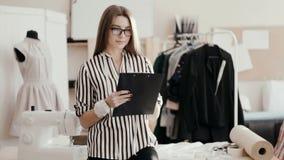 O desenhador de moda da menina faz um esboço do vestido na tabuleta, olhando a câmera e o sorriso Senhora nova do negócio video estoque