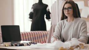O desenhador de moda da menina, no estúdio na tabela com um pano, linha colorida e um portátil, tira um esboço, toma a video estoque