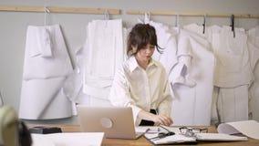 O desenhador de moda escolhe os testes padrões que penduram o para murar em para costurar o estúdio filme