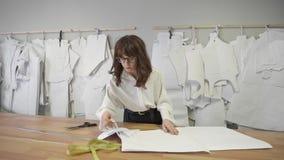 O desenhador de moda escolhe o teste padrão de papel e pendura-o para murar em costura o estúdio vídeos de arquivo