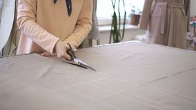 O desenhador de moda está cortando o detalhe de roupa no estúdio brilhante filme