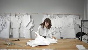 O desenhador de moda está vindo até a tabela olhar através dos testes padrões video estoque