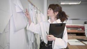 O desenhador de moda está vindo olhar os testes padrões que penduram na parede video estoque