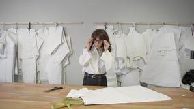 O desenhador de moda fêmea está vindo apresentar com testes padrões de papel filme
