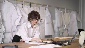 O desenhador de moda fêmea que trabalha dentro costura o estúdio com portátil vídeos de arquivo