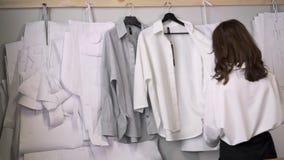 O desenhador de moda na camisa branca de suspensão da cremalheira ao longo da parede costura dentro o estúdio vídeos de arquivo