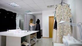 O desenhador de moda na roupa ocasional está fazendo medidas do vestido usando o manequim na oficina da costura Imagem de video estoque