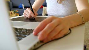 O desenhista da mulher tira em uma tabuleta de gráficos Mulher que trabalha com o portátil no escritório em casa vídeos de arquivo