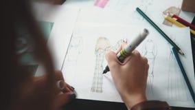 O desenhista da roupa faz um esboço da roupa com uma caneta com ponta de feltro A fêmea entrega o close up video estoque