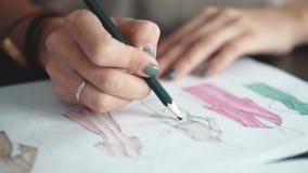 O desenhista da roupa faz um esboço da roupa com uma caneta com ponta de feltro A fêmea entrega o close up filme