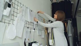 O desenhista de roupa criativo novo está olhando os esboços que penduram então os na parede acima da tabela do estúdio ao lado de vídeos de arquivo