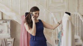 O desenhista e a costureira novos da roupa sorriem e verificam a camisa e as negociações telefonam no estúdio do alfaiate