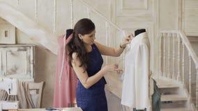 O desenhista e a costureira novos da roupa verificam a camisa do tamanho com a régua no estúdio do alfaiate
