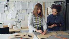 O desenhista fêmea da roupa está tirando esboços do vestuário novo na tela com giz quando seu colega a ajudar e video estoque