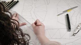 O desenhista fêmea faz um desenho de trabalho Local de trabalho de um desenhista do brinquedo Os marcadores, a régua, a pena e o  imagens de stock royalty free