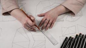 O desenhista fêmea faz um desenho de trabalho Local de trabalho de um desenhista do brinquedo Os marcadores, a régua, a pena e o  imagem de stock