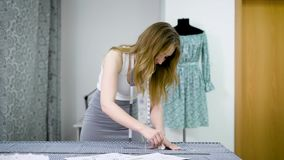 O desenhista fêmea novo com fita-linha em seu pescoço que está no estúdio da costura e que tira alinha com giz e regra video estoque