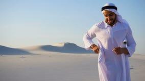O desenhista masculino Arabian Sheikh de Emirati termina o exame do local para o canteiro de obras e responde ao telefonema do `  video estoque
