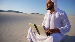 O desenhista profissional UAE do xeique árabe de Emirati com projetos de computador projeta-se, sentando-se na areia no deserto n vídeos de arquivo