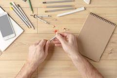 O desenhista tira um esboço em um caderno em uma tabela de madeira stationery Vista de acima imagem de stock royalty free