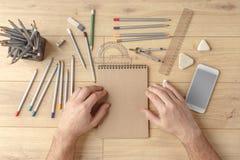 O desenhista tira um esboço em um caderno em uma tabela de madeira stationery Vista de acima fotos de stock royalty free